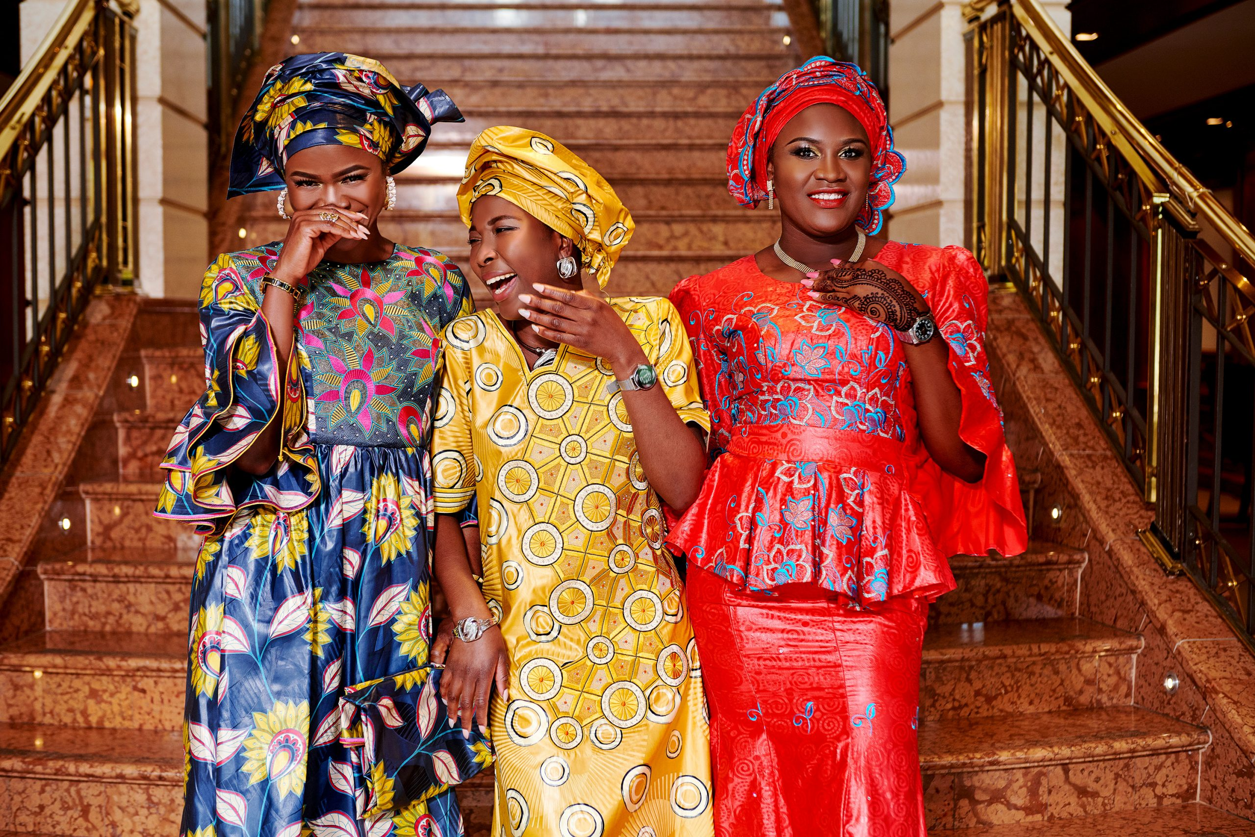 3 woman standing together in 3 colorful bazin dresses